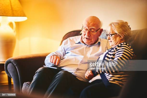 Relaxed elderly couple using digital tablet at home