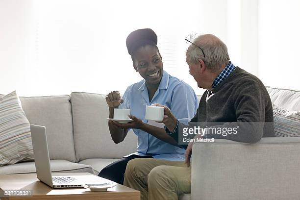 relaxed elderly man and female nurse having coffee - house call stock photos and pictures
