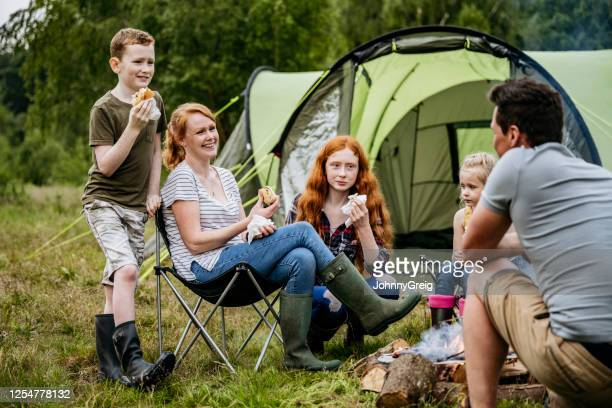 relaxed family enjoying cookout on weekend camping trip - uk stock pictures, royalty-free photos & images