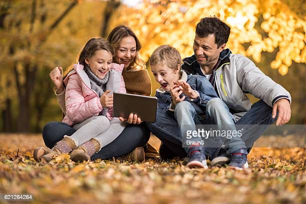Relaxed family using digital tablet in autumn leaves.