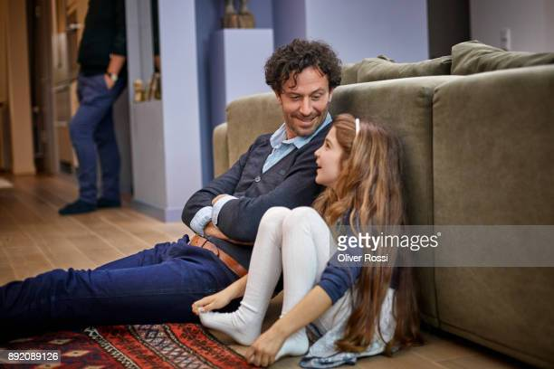 relaxed father and daughter sitting in living room leaning against couch - little girls in tights stock photos and pictures