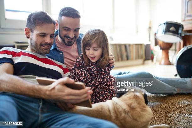 relaxed fathers and 3 year old daughter using digital tablet - southern european descent stock pictures, royalty-free photos & images