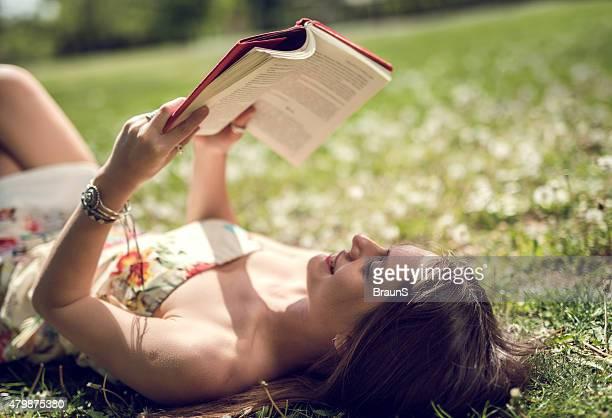 Tranquilo estudiante mujer disfrutando al aire libre y en el aprendizaje de un libro.