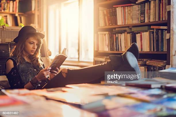 Tranquilo estudiante mujer leyendo un libro en la biblioteca.