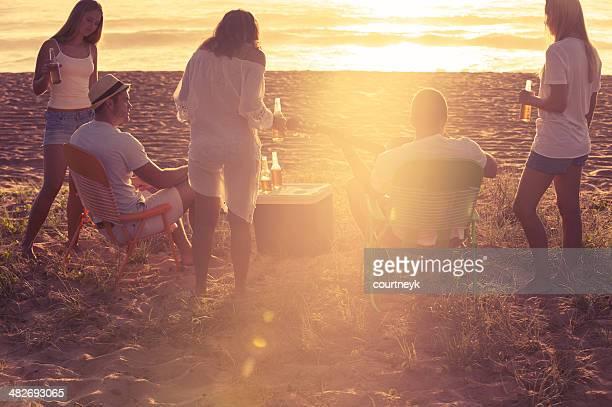 Tranquilo amigos de fiesta en la playa al atardecer