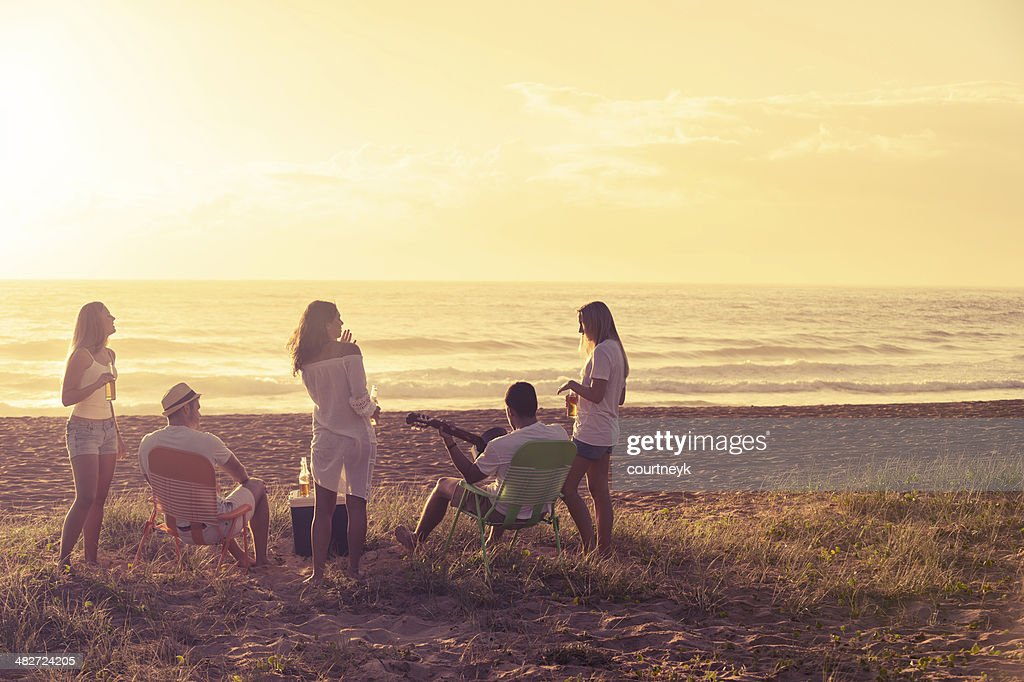 Relaxed friends beach party at sunset : Stock Photo