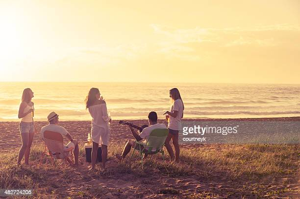 Relaxed friends beach party at sunset
