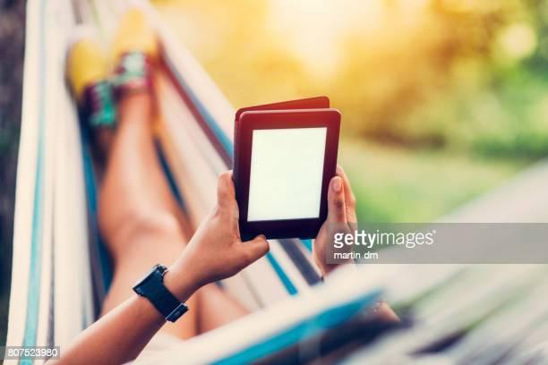 Ontspannen meisje in hangmat lezen van een e-boek