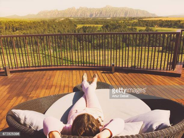 Relaxed girl laying in big couch on the terrace outdoor with good weather in springtime contemplating the landscape view with Montserrat mountain range in the background during weekend activities in the Catalonia region.
