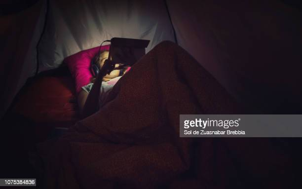 Relaxed girl watching videos and listening to music on her digital tablet inside a tent