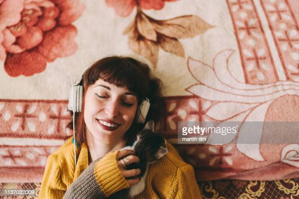 Relaxed girl with cat enjoying good music at home