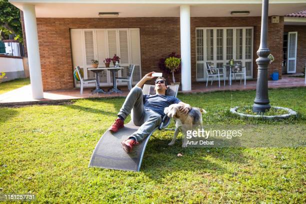 relaxed guy listening music with mobile phone and dog in the backyard house. - deck chair stock pictures, royalty-free photos & images