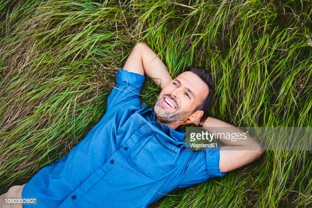 relaxed happy man lying in grass - hands behind head stock pictures, royalty-free photos & images