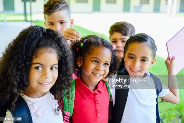 relaxed hispanic schoolchildren walking together outdoors - nosotroscollection stock pictures, royalty-free photos & images