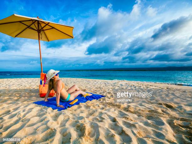 relaxed hispanic young woman sitting and sunbathing on a tropical turquoise caribbean cay beach - ombrellone da spiaggia foto e immagini stock