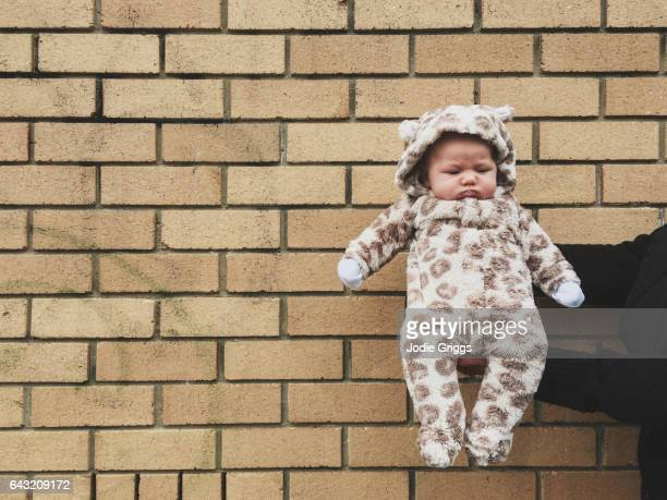 Relaxed infant wearing warm fluffy suit being held out in front of a brick wall