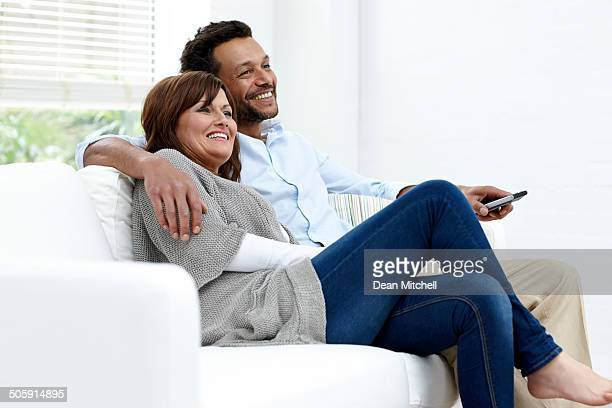 Relaxed interracial couple enjoying watching TV at home