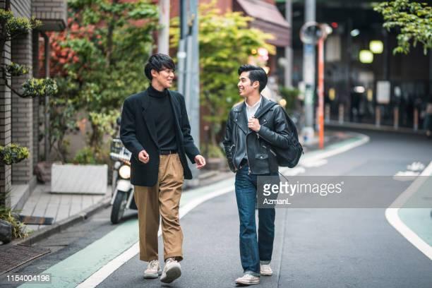 東京で歩いて話をする日本の男性の友達をのんびり - レザージャケット ストックフォトと画像