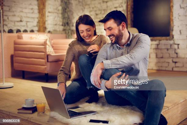 relaxed loving young couple with laptop at home - emir memedovski stock pictures, royalty-free photos & images