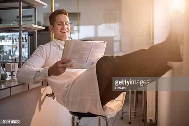 Entspannte männlichen Arzt Medizin zu lesen Buch im Labor.