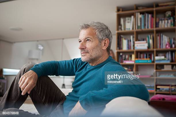 Relaxed man at home sitting on couch