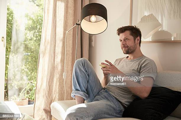 relaxed man at home sitting on couch with cell phone - lamp stock-fotos und bilder
