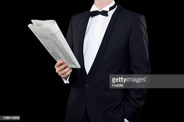 A relaxed man in a tuxedo casually reading the financial section
