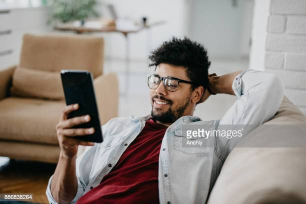 Relaxed man in cozy apartment using digital tablet