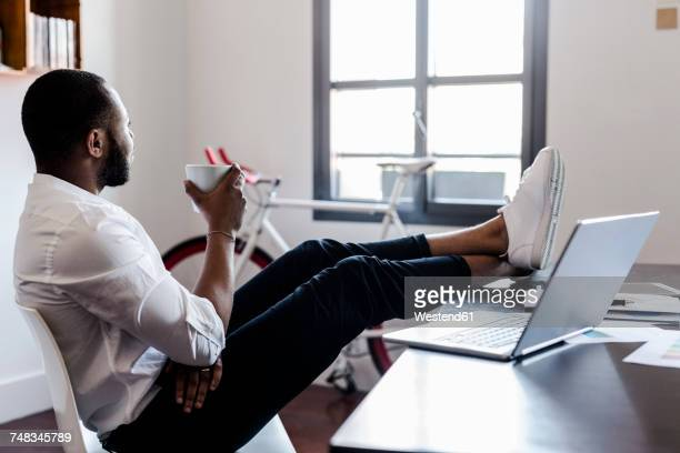 Relaxed man in home office with feet on desk