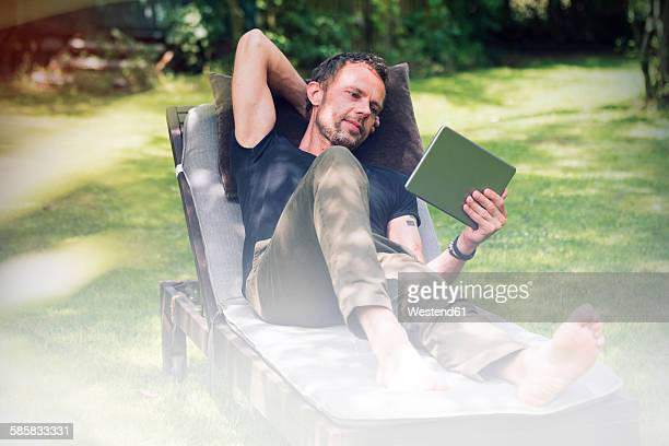 Relaxed man lying in sun lounger in garden using digital tablet