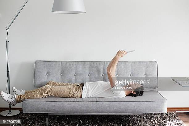relaxed man lying on couch holding digital tablet - lying down foto e immagini stock