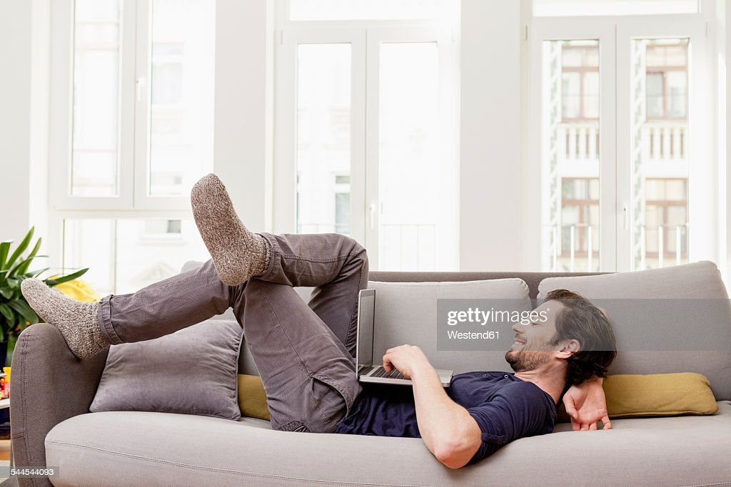 Relaxed man lying on couch using laptop : Stock Photo