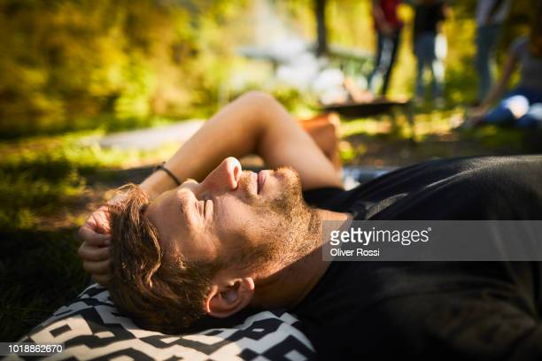relaxed man lying outdoors on cushion - wochenendaktivität stock-fotos und bilder