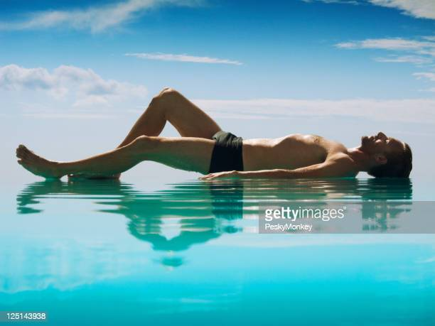 Relaxed Man Lying Reflecting on Infinity Pool