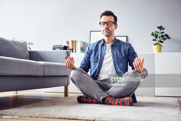 relaxed man meditating at home - meditieren stock-fotos und bilder