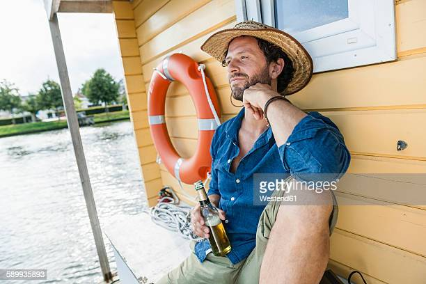 Relaxed man on a house boat with beer bottle