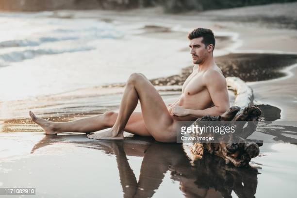 relaxed man on the beach sand - naturist male stock pictures, royalty-free photos & images