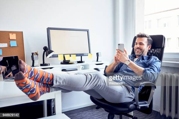 relaxed man sitting at desk in office using cell phone - men in white socks fotografías e imágenes de stock