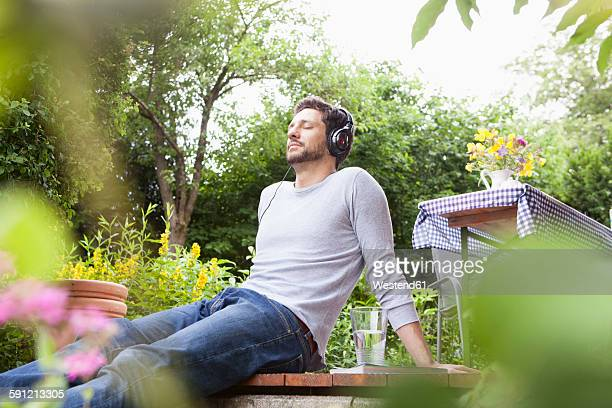 Relaxed man sitting in garden with headphones