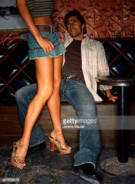 relaxed man sitting on a seat in a bar looking up at a woman wearing a mini skirt - legs and short skirt sitting down stock photos and pictures