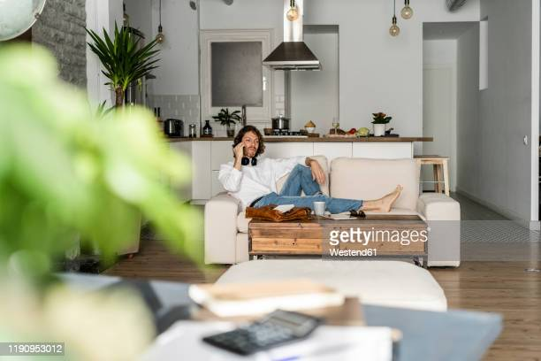 relaxed man sitting on couch at home talking on the phone - focus on background ストックフォトと画像
