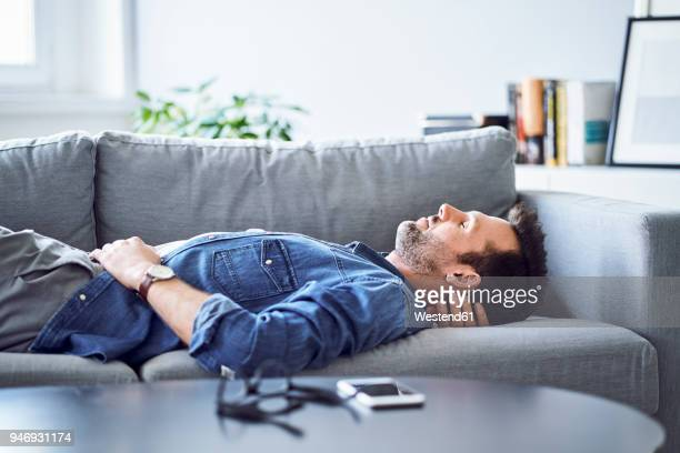 Relaxed man sleeping on sofa