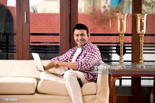 relaxed man using laptop while sitting on sofa - 35 39 years stock pictures, royalty-free photos & images