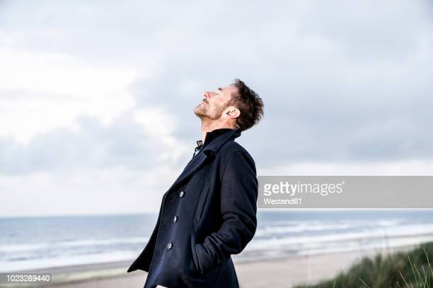 relaxed man with closed eyes on the beach - freedom stock pictures, royalty-free photos & images