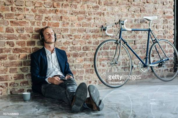Relaxed man with headphones leaning against brick wall