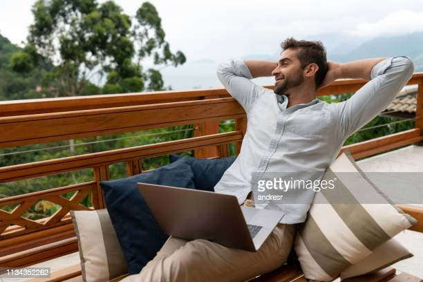 relaxed man working online at home on the balcony using a laptop computer - serene people stock pictures, royalty-free photos & images