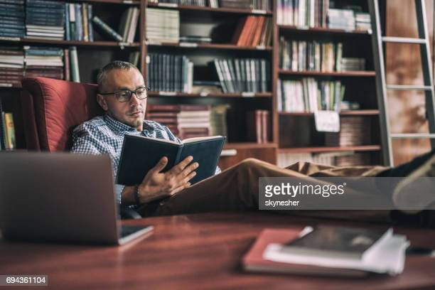 Relaxed manager reading a book at his home office.