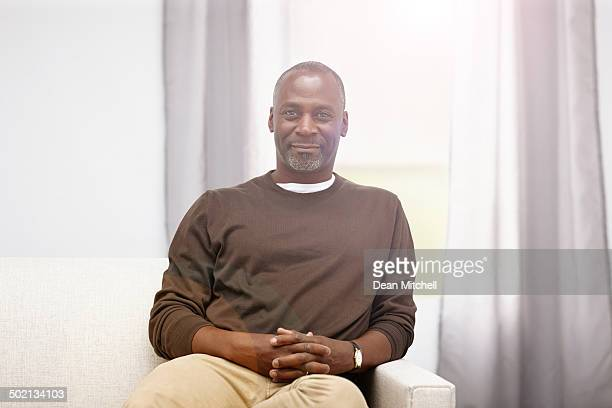relaxed mature african man sitting on sofa - most handsome black men stock photos and pictures