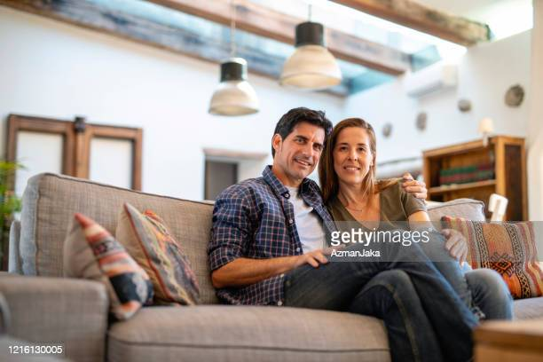 relaxed mature couple sitting close on sofa in family home - southern european descent stock pictures, royalty-free photos & images