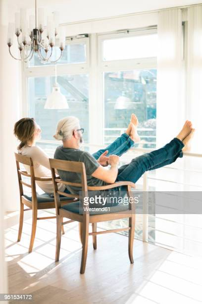 relaxed mature couple sitting on chairs at home with feet up - hoch allgemeine beschaffenheit stock-fotos und bilder